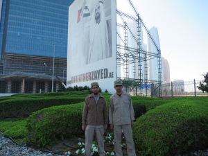 Two builders in front of a billboard of Sheikh Zayed, Abu Dhabi.